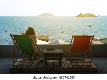 woman sit alone with one empty chair on deck : loneliness concept