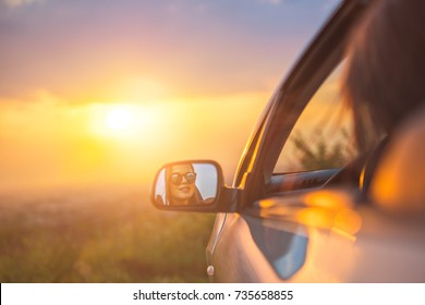The woman sit in a car on the background of the sunset