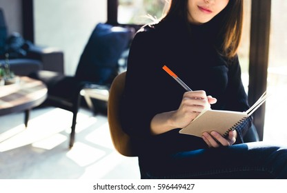 woman sit down to writing a notebook on her legs.
