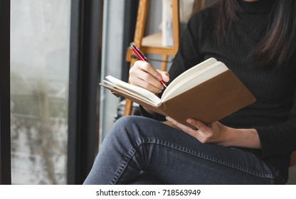 woman sit down to writing a notebook on her legs