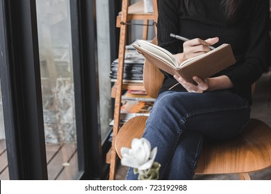 woman sit down to writting a notebook on her legs