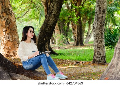 Woman sit drawing  on notebook in  garden