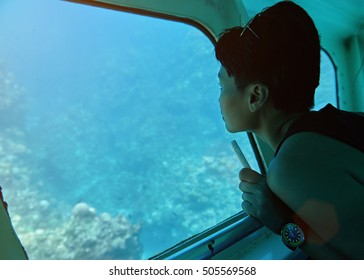 woman sit in glass bottom boat next to window