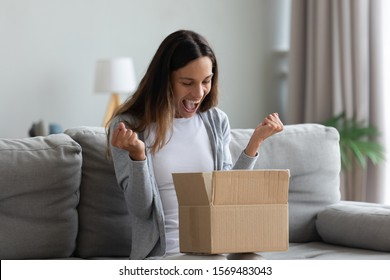 Woman sit on couch screaming with joy opens carton box feel happy, addressee girl received long-awaited package, fast easy and quick post mail parcel delivery, reliable postal courier service concept