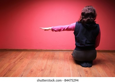 woman to sit on floor on red wall background