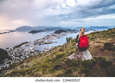 Woman sit on mountaintop looking towards ocean city aalesund norway