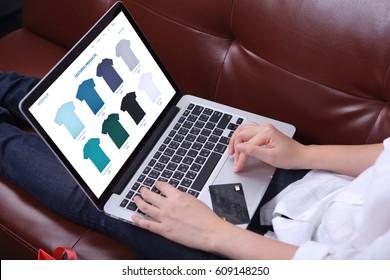 Woman sit on sofa with choosing tshirt on ecommerce webshop