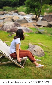Woman Sit and Relax on the Beach Chair Beside The Stream