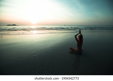 Woman sit at the seaside and meditating in yoga pose during amazing sunset.