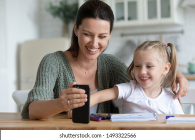 Woman sit at table in kitchen with little daughter distracted from drawing or study having fun using smartphone, new online apps usage, internet amusements or education program learn with kids concept