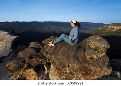 Woman site on a rock and looks at the landscape from Lincoln Rock Lookout at sunrise in the Blue Mountains National Park in the Blue Mountains region of New South Wales, Australia