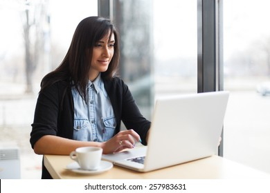 woman siting with coffee and using laptop in cafe