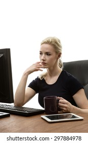 woman siting at her desk working and drink from a cup