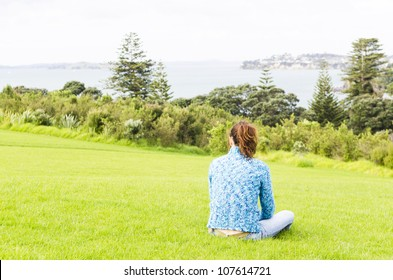 A woman sits alone and feels depressed in a public park overlooking the sea.