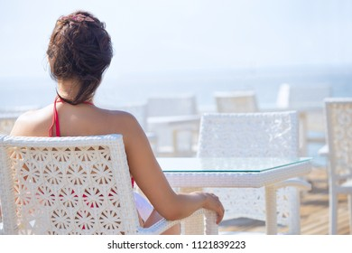 A woman sits alone in a restaurant on the beach and looks at the sea. The concept of enjoying solitude and tranquility.