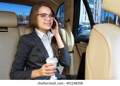 Woman sits in the car and speaks by phone