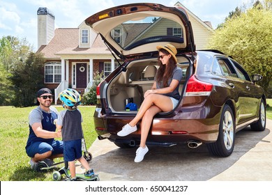 Woman sits in cars trunk and smiling.Men and toddler boy with kickboards playing together.Happy family time.Mother,father,son near house in suburban neighborhood.Warm weather,green grass,summer.