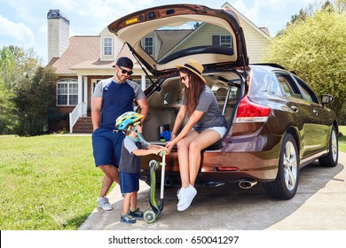 Woman sits in cars trunk and smiling.Men stands near vehicle.Toddler boy holding kickboard.Happy family time.Mother,father,son near house in suburban neighborhood.Warm weather,summer.