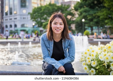 A woman sits at a fountain in Odori Park, the largest in Sapporo, Japan; the park draws large crowds during summer for its many beer gardens, grassy spaces, fountains, and flowers