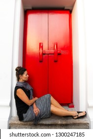 Woman sits in front of vintage wooden red doors