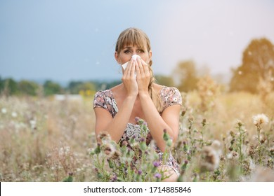 A woman sits in a hay meadow and snorts in a handkerchief