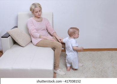 woman sits with her child, postpartum depression