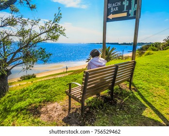 a woman sits on a bench at beach side with beautiful weather