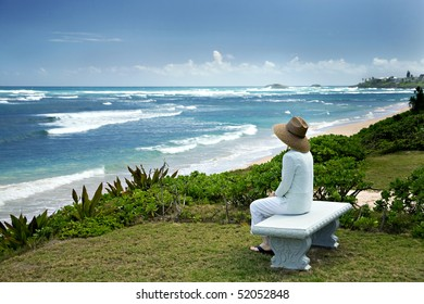 A woman sits on a bench overlooking a beautiful view of the beach in Hawaii.