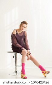 A woman sits on a chair in a black skirt and a fiolet sweater, pink socks and gold sandals, golden accessories, clothing style 70's 80's.