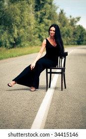woman sits on a chair on the road