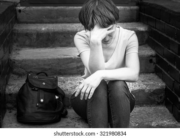 A woman sits on the concrete stairs in a very depressed mood, lying next to her on the stairs of her backpack.