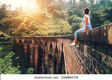 Woman sits on the Demodara nine arches bridge the most visited sight of Ella town in Sri Lanka