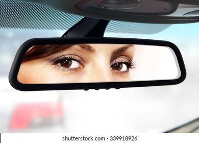 Frau sitzt auf dem Fahrersitz und sieht im Rückspiegel aus