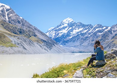 Woman Sits on the Edge of Hooker Glacier Lake with Aoraki Mt. Cook in the Background