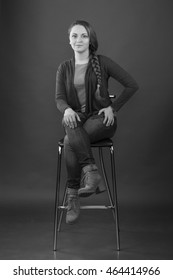 Woman sits on a high chair on gray background. Black and White Photo