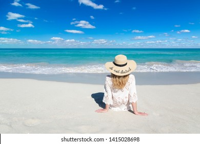 Woman sits on ocean beach in Cuba, wearing hat, beautiful sky and water, Do not disturb, perfect background, free space