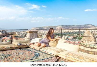 A woman sits on one of the Cappadocia roof. Romantic scene, Cappadocia, Goreme, Turkey.