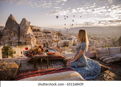 A woman sits on one of the Cappadocia roof in early morning sunrise, when balloons fly. Romantic scene Cappadocia, Turkey.