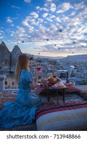 A woman sits on one of the Cappadocia roof in early morning sunrise, when balloons fly. Romantic scene Cappadocia, Turkey