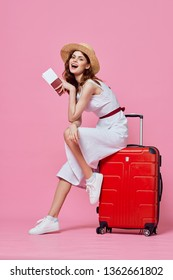 A woman sits on a red suitcase with her leg bent over and holds tickets for a trip