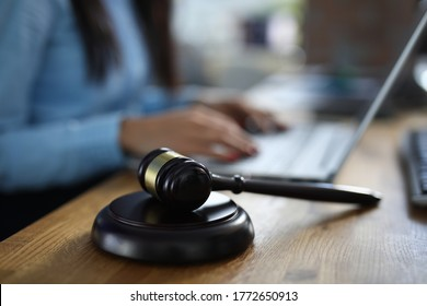 Woman sits on table next to her lies wooden gavel for court hearings. Modern judicial justice concept