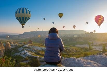 woman sits on top of Cappadocia hill in early morning sunrise, when balloons fly. Romantic scene Cappadocia, Turkey
