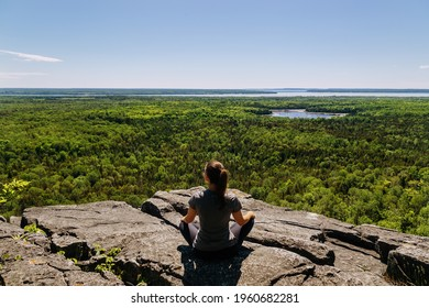 A woman sits on top of a rock and looks at the woods in front of her at Michigiwadinong the Cup and Saucer trail in Manitoulin island, Ontario, Canada