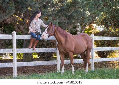 A woman sits on a white ranch fence petting her horse.