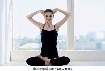 A woman sits on the windowsill and is engaged in meditation