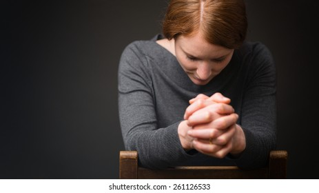 A woman sits on a wooden chair and prays to God.