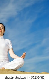 woman sits quietly in the lotus position on sand