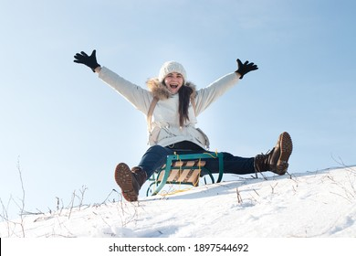 Woman sits and sledges from the mountain against the background of snow and sky in winterGirl laughs and rejoices in snow, entertainment in the sled.