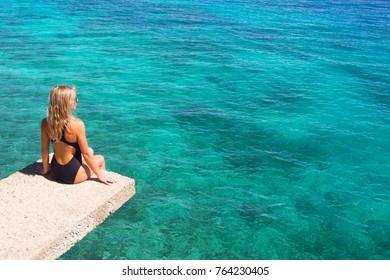 Woman sitting above beautiful blue sea. Back view.