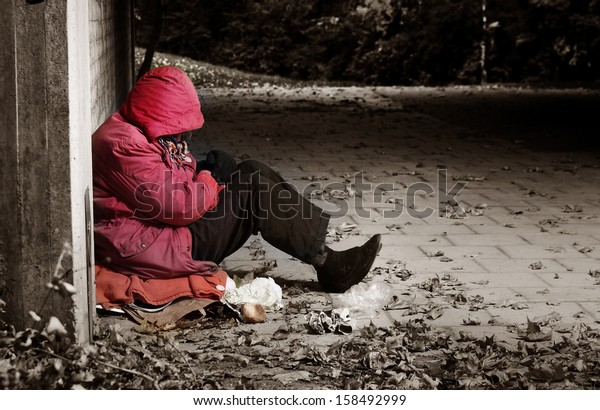 A woman sitting against a brick building with her head in her arms